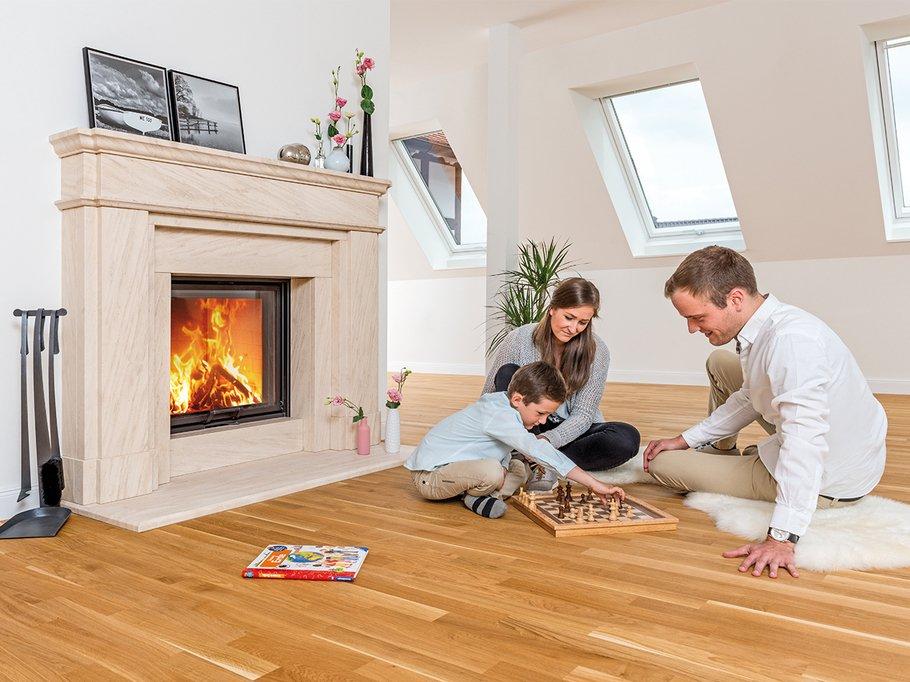 Durch Einsatz einer modernen Heizkassette wird aus einem offenen Kamin ein geschlossener mit Sichtscheibe. Vater mit Frau und Sohn spielen davor sitzend am Boden Schach